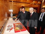 Nguyen Phu Trong et Bounnhang Vorachith à une exposition sur les relations Vietnam-Laos